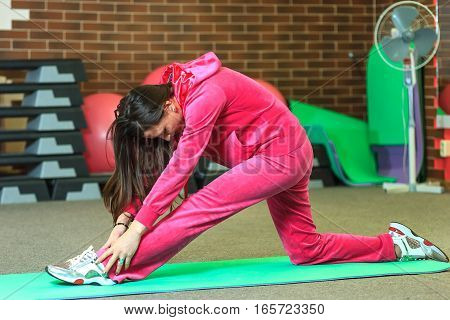 Young Beautiful White Girl In A Pink Sports Suit Does Physical Exercises At The Fitness Center. Hall