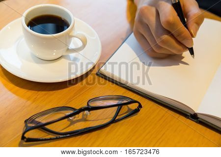man notebook with pen and coffee and glasses on wooden table
