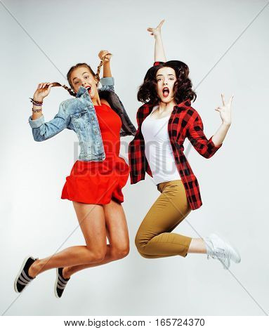 two pretty brunette and blonde teenage girl friends jumping happy smiling on white background, lifestyle real people concept close up