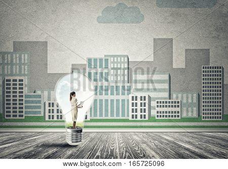 Businesswoman inside light bulb against city drawn concept
