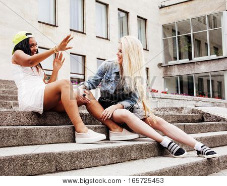 Two teenage girls infront of university building smiling, having fun, lifestyle people concept, diverse nations close up