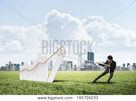 Young man outdoors and growing graph presenting growth progress