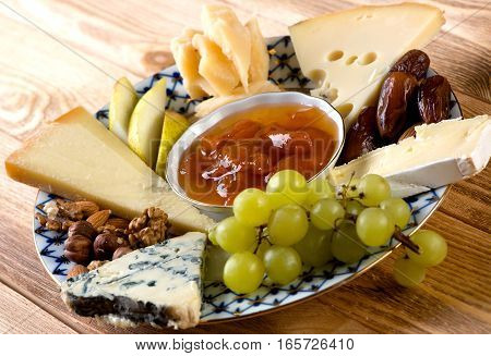 Different kids of cheese grapes and nuts on plate