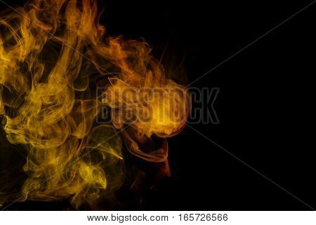 Abstract smoke Weipa. Personal vaporizers fragrant steam. The concept of alternative non-nicotine smoking. Yellow smoke on a black background. E-cigarette. Evaporator. Taking Close-up. Vaping.
