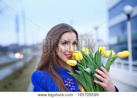 Young attractive girl in a blue coat and yellow dress holding a bouquet of yellow tulips. Spring is coming to town. She sniffs flowers. Close-up portrait.