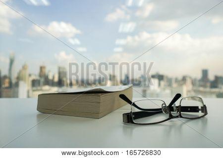 men glasses beside the book for reading