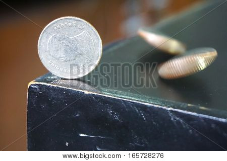 The Thai baht currency coin on the table in a vertical position with a moving coin.