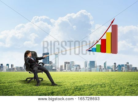 Young man in chair outdoors and growing graph presenting growth progress