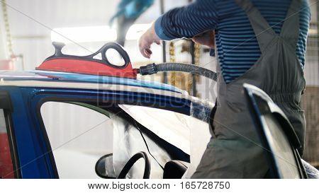 Automobile service - manual labor - polishes car, close up, wide angle