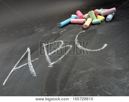 ABC written on a blackboard with chalk in background