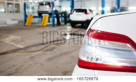 Automobile service - mechanics checking lifted car, defocused background, slider