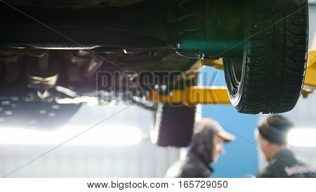 Car lifted in automobile service for fixing, water flows from the wheel, close up