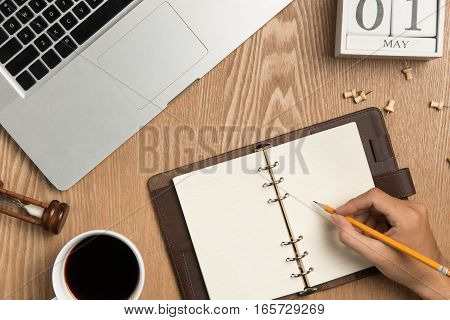 Business planning concept and new year's resolutions concept. Top view of hand writing on a blank notebook with hot coffee.