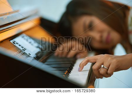 Female pianist touching piano key with her finger, selective focus