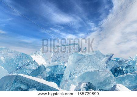 Blocks of broken blue ice on sky background