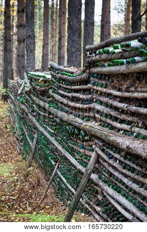 A fence made with pine logs and empty champagne bottles in the forest at the Eurasian line near Yekaterinburg Russia.  The champagne has been used to toast newly wedded couples and to celebrate special occasions. Shallow depth of field.