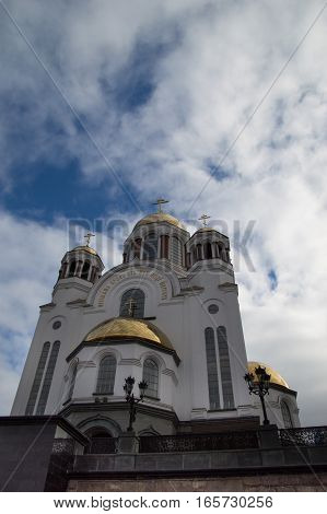 Russian Orthodox Church of All Saints built onot the execution site of the Romanovs in Yekaterinburg Russia.  The white facade is topped with golden onion domes and crosses with blue sky and clouds above.