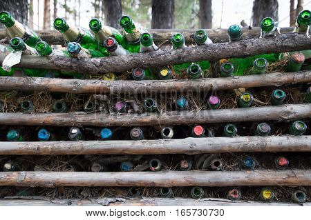 A fence made from empty green champagne bottles and pine logs with pine needles. The empty bottles are placed in the fence after celebrating marriage and other special occasions. Located at the Eurasian line near Yekaterinburg Russia.