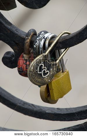 Close up of five padlocks, including a brass lock with heart shaped rhinestones, on a portion of black metal fence.  The padlocks are placed by couples to celebrate their love and marriage. Located in Yekaterinburg Russia. Shallow depth of field.