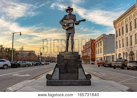 Montgomery Alabama USA - January 17 2017: Statue of Hank Williams the famous country singer on Commerce Street with historic buildings on the right.