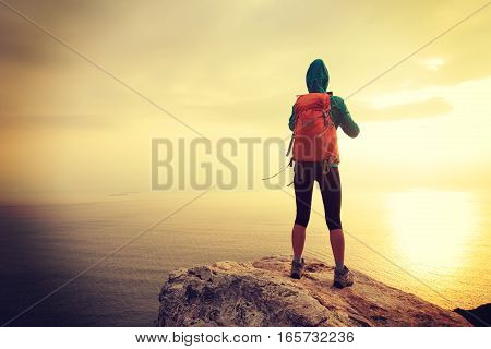 successful hiker use digital tablet taking photo on seaside mountain peak rock