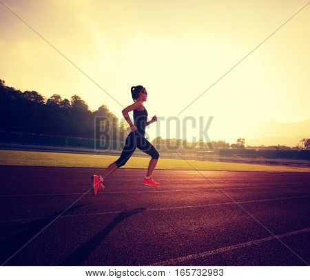 young fitness woman runner running on stadium track