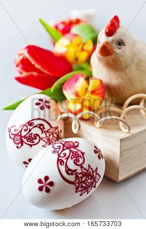 Traditional Czech easter decoration - white eggs with tulip flowers with wooden chicken and tulips. Spring easter holiday arrangement.