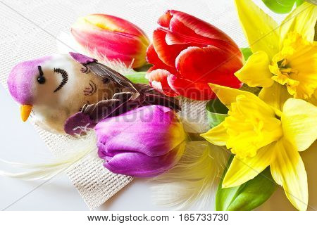 Traditional Czech easter decoration - daffodils and colorful tulips with bird. Spring easter holiday arrangement.