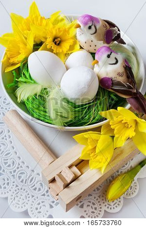 Traditional Czech easter decoration - regional wooden ratchet instrument with white eggs with daffodils and birds in the green grass nest. Spring easter holiday arrangement.