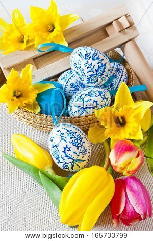 Traditional Czech easter decoration - regional wooden ratchet instrument with painted blue eggs with daffodils and tulips flower in the basket. Spring easter holiday arrangement.