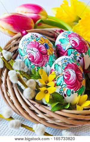 Traditional Czech easter decoration - colorful painted eggs in wicker nest with pussycats and tulips. Spring easter holiday arrangement.