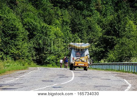 Cyclists supported by technical vehicle during competition on mountain road in Caucasus, Russia