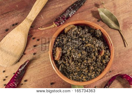 A photo of a lentil stew, shot from above on a dark wooden texture with bay leaves and peppers scattered around it