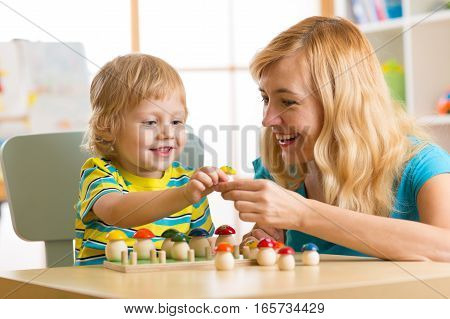 Mother and child son are talking and smiling while playing with educational toys at home