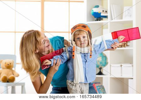 Kid boy dressed like a pilot with toy wings playing at home