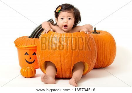 Baby girl in giant pumpkin for Halloween