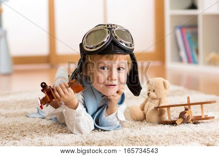 Concept of dreams and travels. Child weared pilot or aviator plays with a toy airplane at home in nursery room