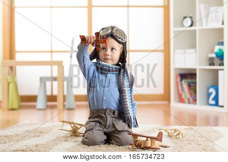 Happy child boy plays with wooden toy airplanes on floor in nursery room