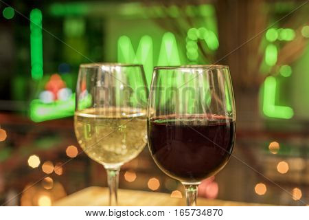 Glasses of red and white wine on a blurred background of lights, selective focus