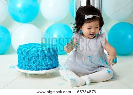 Asian baby girl's first blue birthday cake smashing with balloons decoration.