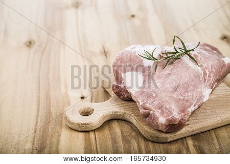 Raw Pork With Rosemary On A Wooden Board On The Table. Cooking Food.