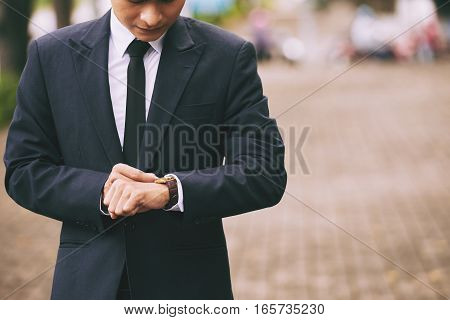 Cropped image of businessman checking time on his wristwatch