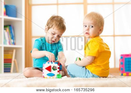 Kids playing with logical toy on soft carpet in nursery roomor kindergarten. Children arranging and sorting shapes and sizes.