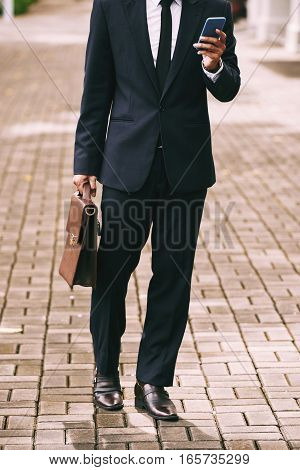 Businessman in suite with briefcase and smartphone
