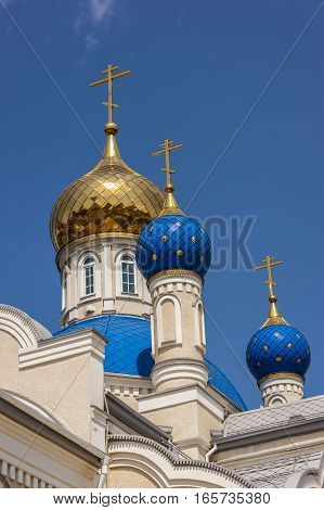 Russia Rostov- on-Don. Orthodox Church of Our Lady of Kazan . Gold-plated and blue with gold stars Domes against a bright blue sky .