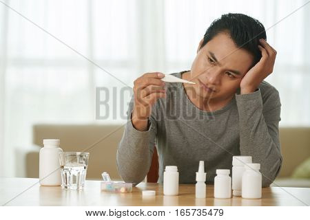 Unhealthy Asian young man checking his temperature