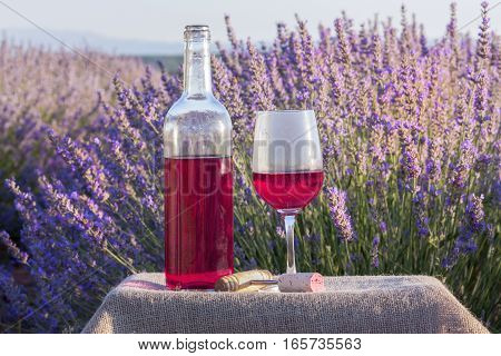 A vibrant photo of a rose wine glass and a bottle in a lavender field, with a retro corkscrew and a cork, slightly toned