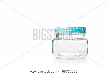 empty glass jar with blue dotted lid on white background copyspace on left