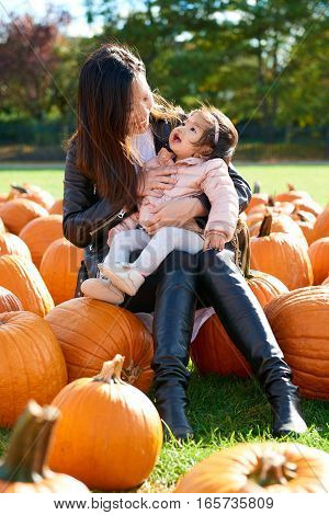 Mother holding daughte and sit on pumpkin