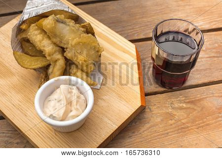 Fish and chips with a tartar sauce and a glass of red wine, on a wooden table with copy space. An English dish served in a traditional Spanish cucurucho, cone, and with a chato glass